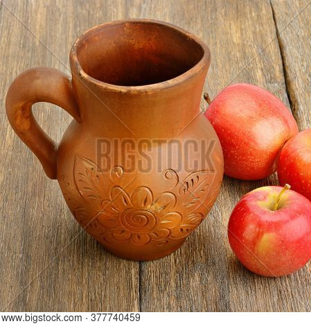 Apple Cider In A Ceramic Jug On A Wooden Table.
