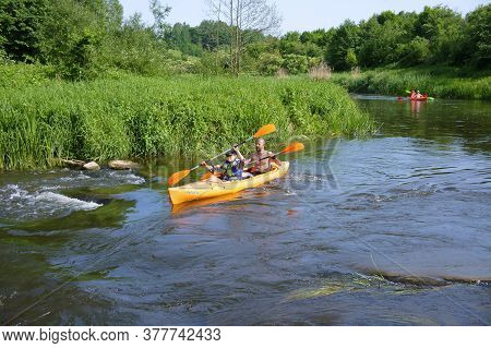 A Man Floating On A Kayak, Tourists To Raft On A Canoe On The River, Angrapa River, Kaliningrad Regi