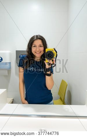 The Girl Photographs Herself In The Mirror In The Women's Toilet. Selfie On The Camera In The Women'