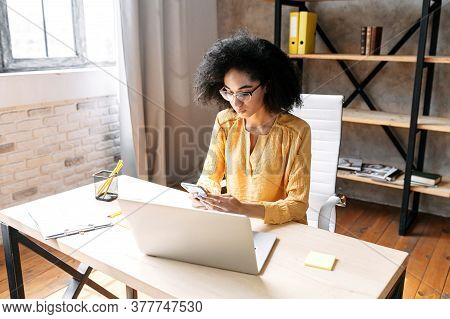 Attractive African American Business Woman Is Using Mobile Phone While Sitting At The Desk With Lapt