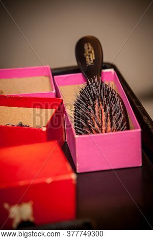 Pink And Black Hair Brush In A Pink Box On A Make Up Table. High Quality Photo
