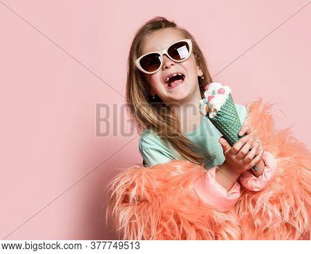 Frolic Kid Girl In Faux Fur Coat Holds With Both Hands Big Ice Cream In Waffles Cone Decorated With