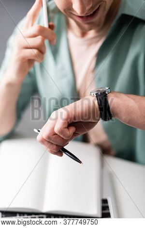 Cropped View Of Smiling Freelancer Checking Time While Talking On Smartphone And Holding Pen, Concep