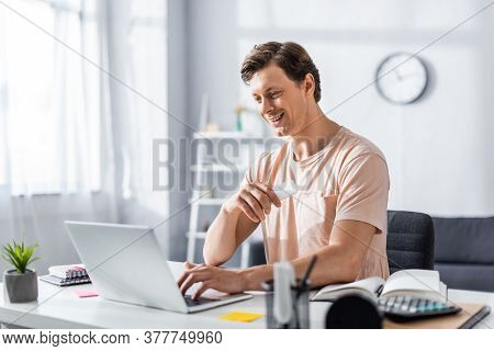Smiling Teleworker Looking At Laptop And Sitting At Table With Stationery At Home, Earning Online Co