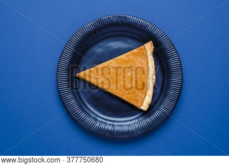 One Slice Of Pumpkin Pie On A Plate, Top View. Above View With A Slice Of Pie On A Blue Background.