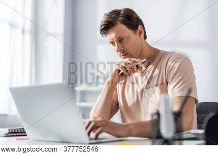 Selective Focus Of Handsome Teleworker Looking At Laptop And Holding Cellphone While Sitting At Tabl
