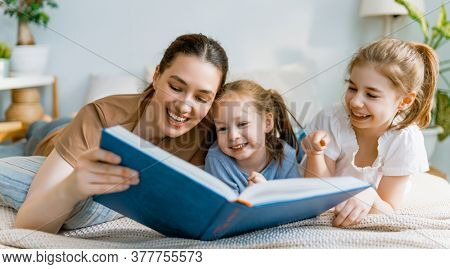 Happy loving family. Pretty young mother reading a book to her daughters on the bed at home.
