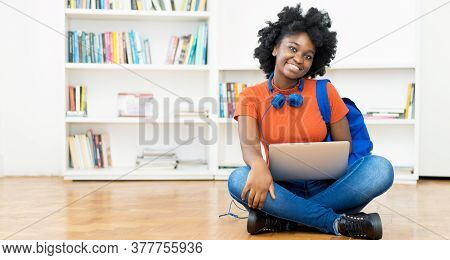 Laughing African American Female Student Learning Online At Computer With Other Students Indoors At