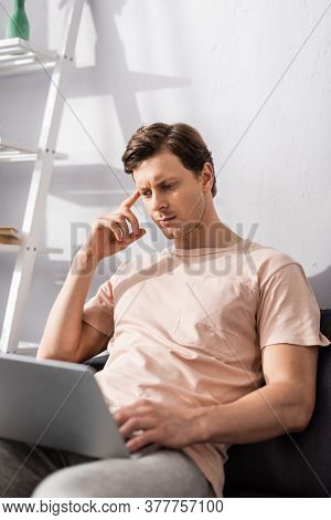 Selective Focus Of Pensive Teleworker Using Laptop On Sofa In Living Room, Earning Online Concept