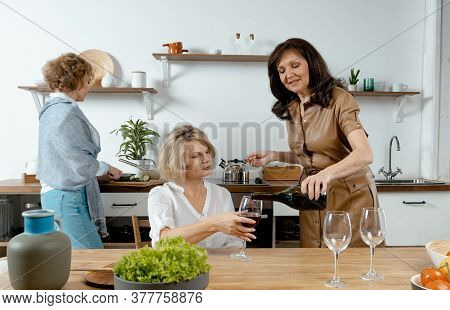 Old Friends Beautiful Senior Women Met For Preparing Meal And Drinking Wine. Concept Of Living Full