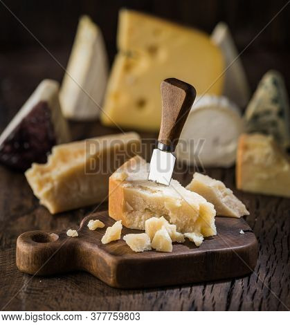 Piece of Parmesan cheese  on the wooden board. Assortment of different cheeses at the background.