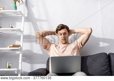Selective Focus Of Concentrated Freelancer With Hands Behind Head Looking At Laptop On Couch, Earnin