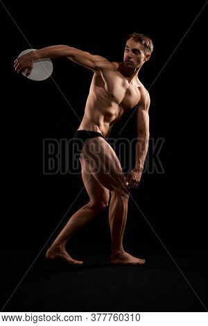 Side View Of Young Athletic Man With Perfect Body And Tensed Muscles Throwing Discus. Isolated Portr