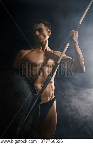 Front View Of Young Athletic Warrior With Perfect Body Throwing Spear. Crop Of Handsome Bodubuilder