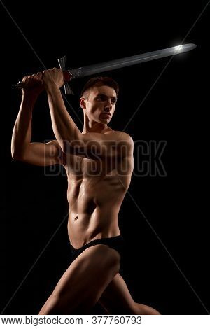 Side View Of Young Fit Strong Warrior With Cold Weapon Looking Away. Muscular Half Naked Athlete Sho