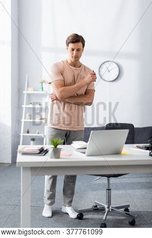 Front View Of Thinking Freelancer Near Laptop And Stationery On Table At Home, Earning Online Concep