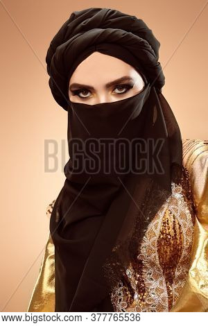 Oriental beauty woman. Portrait of a beautiful arabian woman in traditional look, with traditional oriental make-up and black hijab. Make-up and cosmetics.