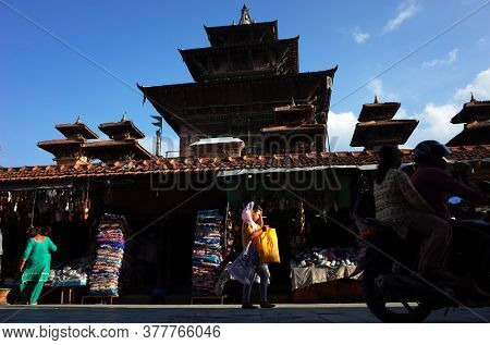 Kathmandu, Nepal - June 20, 2019: Local daily life on street near Durbar square. Young nepali woman with yellow shopping bag walking in sun near traditional nepali architecture temple