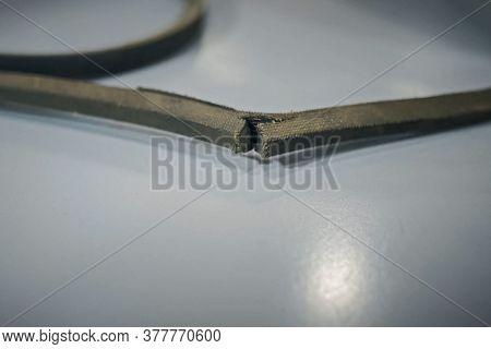 A Torn Rubber Belt Of Belt Transmission.