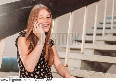 Young, Teen, Ginger Girl Talking On The Phone In Front Of Her School, Sitting On The Stairs