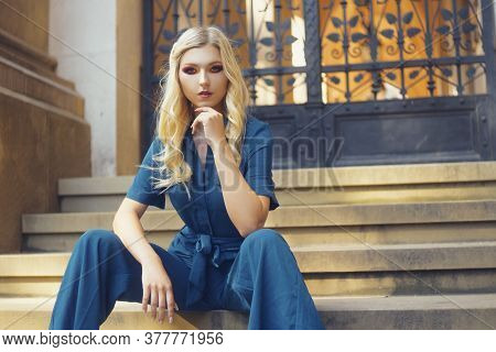 Fashionable Photo Of A Girl, Jumpsuit. Fashionable Style. The Blonde Looks Into The Camera With A Co