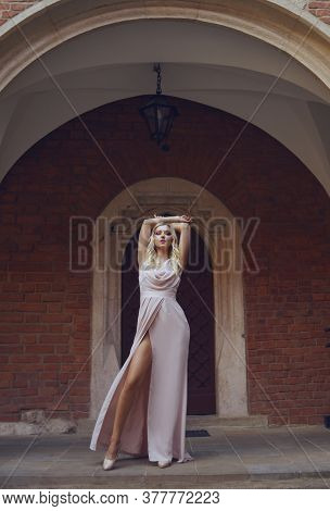 A Girl In A Chic Long Dress In Full Growth In The Castle. Blonde Model Posing, Woman With Long Legs.