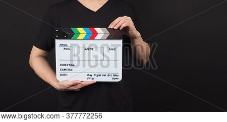 Hand Is Holding Movie Slate.it Is Used In Video Production And Film Industry On Black Background.