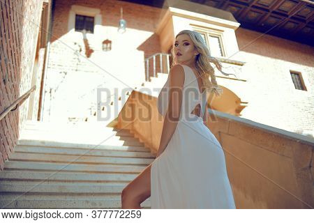 A Posh Woman In A Long White Dress Climbs The Steps To The Castle. The Blonde Looks Over Her Shoulde