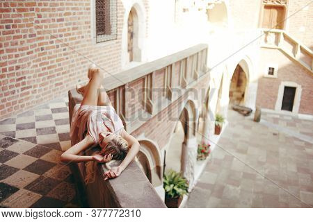 A Beautiful Girl With Long Legs Lies On The Balcony In The Castle. Princess On The Balcony On Vacati
