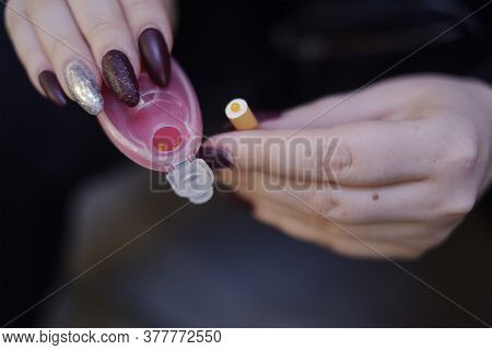 The Girl's Hands Hold Capsules For Cigarettes And Puts Them Into Cigarettes. Banning Flavored Tobacc