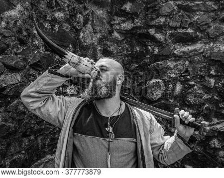 Viking Warrior With Thick Beard And Big Sword Drinks From The Horn