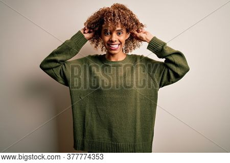Beautiful african american woman with curly hair wearing casual sweater over white background Smiling pulling ears with fingers, funny gesture. Audition problem