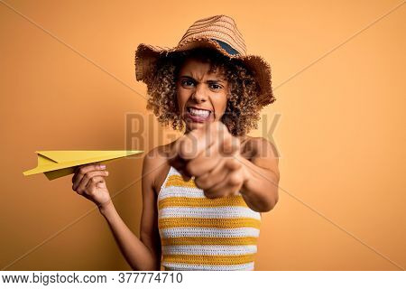 African american tourist woman with curly on vacation wearing summer hat holding paper plane annoyed and frustrated shouting with anger, crazy and yelling with raised hand, anger concept