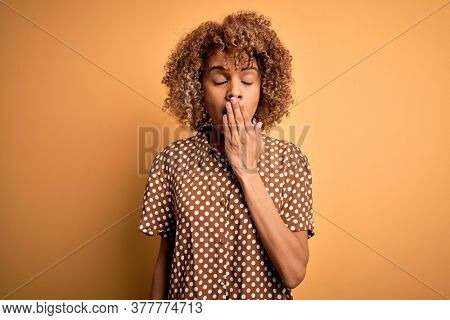 Young beautiful african american woman wearing casual shirt standing over yellow background bored yawning tired covering mouth with hand. Restless and sleepiness.