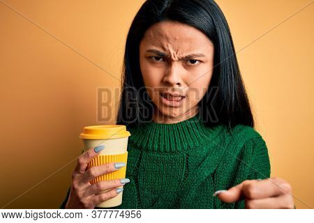 Young beautiful chinese woman drinking cup of coffee over isolated yellow background annoyed and frustrated shouting with anger, crazy and yelling with raised hand, anger concept