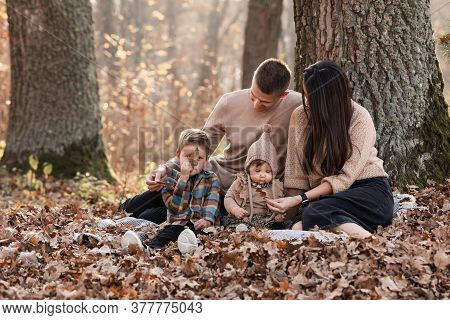 Happy Young Family With Two Little Children Relaxing And Having Fun In Autumn Park On Sunny Day.