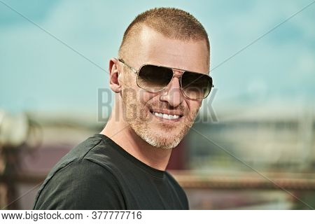 Portrait of a handsome brutal mature man with short hair and bristles wearing trendy sunglasses outdoor. Men's style. Optics for men.