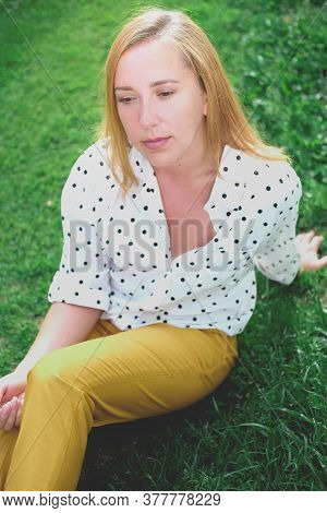 Beautiful Middle Age Woman Sitting On A Grass. Thoughtful Girl Wearing Trendy Polka Dot Blouse And Y