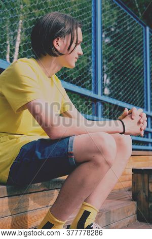 Teenager Boy Sitting On Wooden Stairs On Basketball Playground And Watching A Game. Serious Hipster