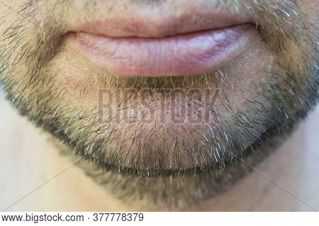 Mature Mans Unshaven Chin Fragment. Bottom Part Of Mens Face With Bristles. The Smile Of An Unshaven