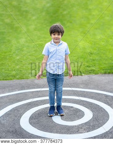 Full Lenght Portrait Kid Standing On Circle Line At Asphalt, Active Kid Playing In Green Field At Th