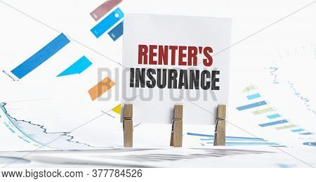 Renters Insurance Text On Paper Sheet With Chart, Dice, Spectacles, Pen, Laptop And Blue And Yellow