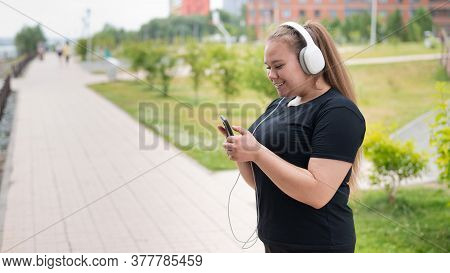 A Beautiful Fat Girl In Black Sportswear Listens To Music On Headphones And Text Messages On The Pho