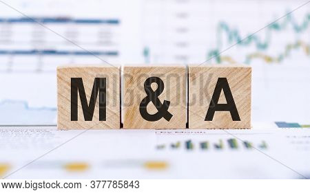 M And A Or Merger And Acquisition Made With Wood Building Blocks On Background From Financial Graphs
