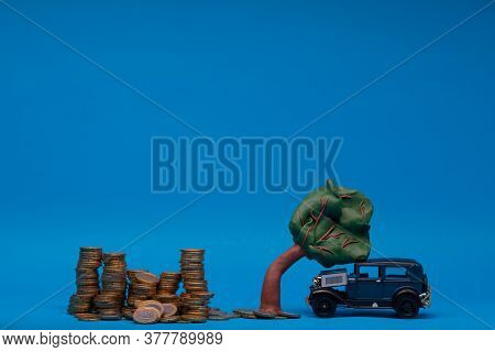 Huge Pile Of Coins Next To A Blue Car Figurine Which Is Sitting Under A Curved Plasticine Tree, On B