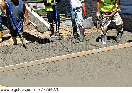 Concrete Workers Screeding, Leveling, And Filling A Patio With Wet Mud.