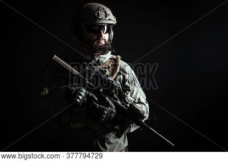 American Commando In A Military Uniform With A Weapon Looks At Copy Space, A Marine On A Dark Backgr