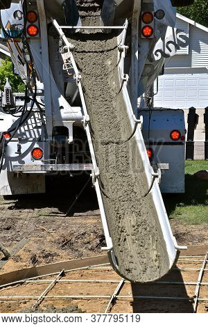 Wet Concrete Works It Way Down The Chute Of A Ready Mix Truck For A New Patio Project