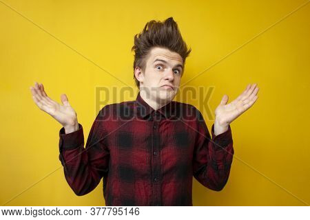 Young Guy Shrugs On Yellow Isolated Background, Hipster With Funny Hairstyle At A Loss