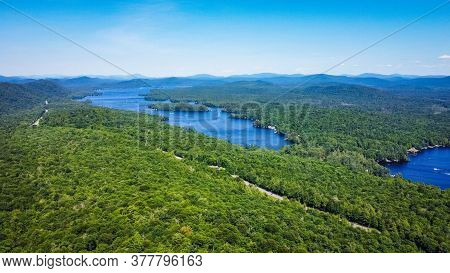 Scenic Aerial View Of A Blue Lake With Pine Trees Coast